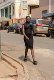 Unidentified Ghanaian woman in black dress with braids walks in. CENTRAL REGION, GHANA - Jan 17, 2017: Unidentified Ghanaian woman in black dress with braids royalty free stock photo