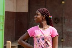 Unidentified Ghanaian woman in pink shirt with braids stands in. CENTRAL REGION, GHANA - Jan 17, 2017: Unidentified Ghanaian woman in pink shirt with braids royalty free stock photos