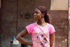 Unidentified Ghanaian woman in pink shirt with braids stands in. CENTRAL REGION, GHANA - Jan 17, 2017: Unidentified Ghanaian woman in pink shirt with braids stock image