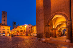 Central square of Alba early in the morning. Arched passage and medieval towers on cobbled town square early in the morning in Alba, Italy Royalty Free Stock Photography