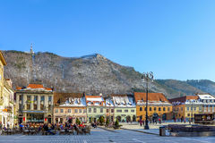 Central Square in Brasov Romania. Brasov, Romania - March 9, 2015: Brasov Town Square with people sitting at cafes and benches during sunny winter afternoon Royalty Free Stock Photo