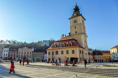 Central Square in Brasov Romania. Brasov, Romania - March 9, 2015: Brasov Town Square with people sitting at cafes and benches during sunny winter afternoon Royalty Free Stock Photography