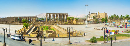 The central square. LUXOR, EGYPT - OCTOBER 8, 2014: Panorama of the ancient Luxor temple, neighboring with the small market and amusement park, on October 8 in Stock Photography