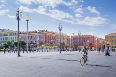 Nice, Provance, Alpes, Cote d`Azur, French,August 15, 2018: View of the place Massena square with people riding a bike. royalty free stock photo