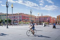Nice, Provance, Alpes, Cote d `Azur, French, August 15, 2018; View of the place Massena square with people riding a bike stock photos