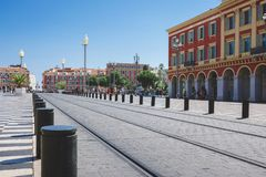Nice, Provance, Alpes, Cote d`Azur, French  July 31, 2018; Tram road on Place Massena with red building and street lights. stock photo