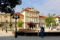 Central square in the town of Smederevo, Serbia. Smederevo is city in east Serbia. Couple with kids are walking around fountain. In background is building of royalty free stock image