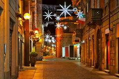 Central street at evening. Alba, Italy. Old city central street with illuminations and decorations for Christmas and New Year celebrations at night in Alba Royalty Free Stock Photography