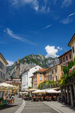 Central streets of Lecco town, with people in outdoor cafe and bell tower. Stock Photos