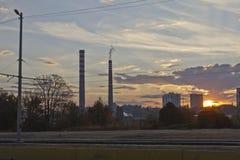 Central térmico de TPP en una salida del sol Refinería con las chimeneas El humo de la fábrica contamina el ambiente T arriba roj foto de archivo