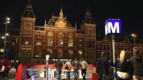 Central Train Station in Amsterdam at Night. AMSTERDAM - CIRCA MAY 2013: Central Train Station and metro entrance in North Holland, the Netherlands. City life at stock footage