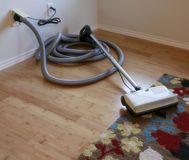 Central Vacuum. Cleaning contest: Beautiful bamboo hardwood floor and wool rug with a central vacuum cleaner attached to the wall Royalty Free Stock Photos