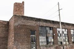 Centrale abandonnée d'école avec Windows cassé et la cheminée de émiettage III de brique Photo stock