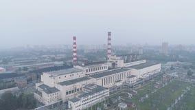 Centrale avec des tuyaux et la ville enveloppée dans la fumée pollution atmosphérique et problèmes écologiques banque de vidéos