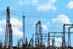 Centrale elettrica elettrica ad alta tensione - pali e linee elettrici sul fondo blu del cielo nuvoloso Fotografia Stock