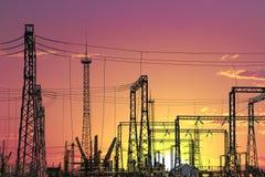 Centrale elettrica elettrica ad alta tensione - pali e linee elettrici sul fondo del cielo nuvoloso di tramonto Immagini Stock Libere da Diritti