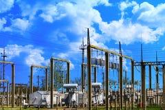 Centrale elettrica elettrica ad alta tensione - pali e linee elettrici sul fondo molto blu del cielo nuvoloso Immagine Stock