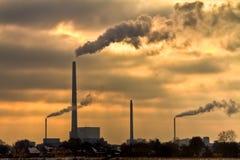 Centrale elettrica con la bruciatura del cielo giallo dietro Fotografie Stock
