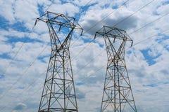 Centrale elettrica di elettricità ad un tramonto Supporto ad alta tensione nuvole nel cielo - riporti in scala il pericolo della  Fotografia Stock