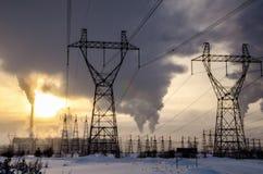 Centrale elettrica nel paesaggio freddo di inverno durante il tramonto Immagine Stock