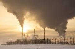 Centrale elettrica nel paesaggio freddo di inverno durante il tramonto Fotografia Stock