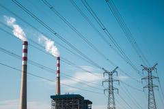 Centrale elettrica termica contro un cielo blu Fotografie Stock