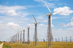 Centrale eolica nel campo Avvolga la centrale elettrica sull'orizzonte, contro un bello cielo blu con le nuvole Industria, fotografia stock