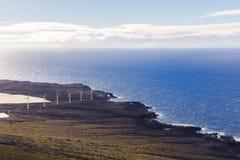 Centrale eolica sulla riva dell'oceano fotografia stock