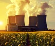 Centrale nucléaire Temelin avec le gisement de graine de colza ou de canola au lever de soleil photos stock