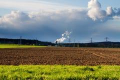 Centrale nucleare con la terra coltivata nella priorità alta Immagine Stock