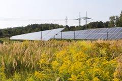 Centrale solaire sur le pré fleurissant d'été Photos libres de droits