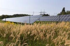 Centrale solaire sur le pré fleurissant d'été Image stock