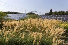 Centrale solaire sur le pré fleurissant d'été Photographie stock libre de droits
