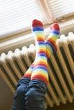 Centrale verwarmingradiator en vrouw in gestreepte sokken stock foto