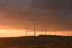 Centrales eléctricas de energía eólica en una puesta del sol Fotografía de archivo