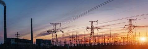 Centrales et lignes électriques thermiques pendant le coucher du soleil Photos libres de droits