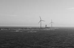 Centrali eoliche sui precedenti in bianco e nero dell'isola Fotografie Stock Libere da Diritti