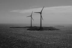 Centrali eoliche sui precedenti in bianco e nero dell'isola Immagini Stock Libere da Diritti