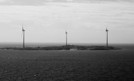 Centrali eoliche sui precedenti in bianco e nero dell'isola Fotografie Stock