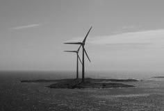 Centrali eoliche sui precedenti in bianco e nero dell'isola Immagine Stock Libera da Diritti