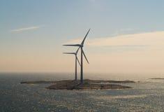 Centrali eoliche sui precedenti dell'isola Immagine Stock