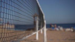 Centrar-se sobre a rede do voleibol no movimento lento na praia do mar vídeos de arquivo