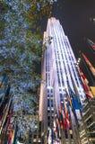 Centre de Rockefeller par nuit avec les drapeaux et les décorations internationaux d'éclairage - New York Photographie stock libre de droits