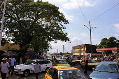 In the centre of Douala, Cameroun. One of the central places in Douala, Cameroun people circulating, motos and cars, daylight Royalty Free Stock Photo