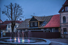 Centre of Kuldiga, Latvia. Colourful fountain at dusk in the centre of Kuldiga, Latvia. Beautiful old buildings in the background with no people Stock Images