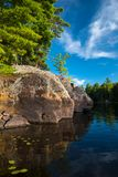 Large rock shoreline in summer royalty free stock photography
