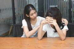 Centre mou de femme asiatique soulageant son ami déprimé dans le salon Image libre de droits