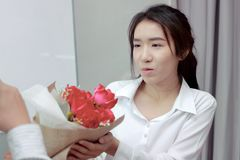 Centre mou de la jeune femme asiatique attirante acceptant un bouquet des roses rouges de l'ami dans le bureau le jour du ` s de  Photographie stock