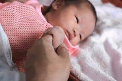 Centre mou de main minuscule nouveau-née de bébé sur le parent photo stock