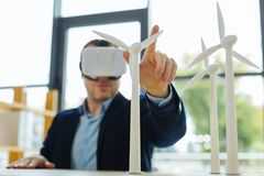 Centre sélectif d'un doigt masculin touchant un modèle de moulin à vent Images libres de droits